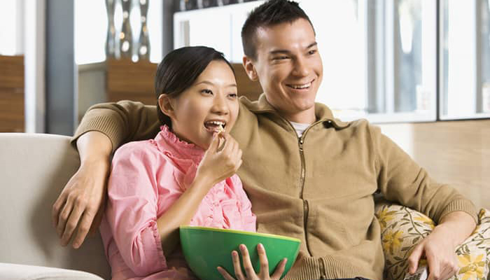 Married Asian couple watching tv on the couch and eating popcorn