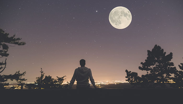 A cancer patient looks up at the stars under a moonlit sky.