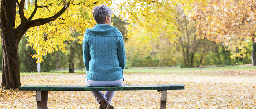 older woman sitting on a bench looking at changing leaves on trees
