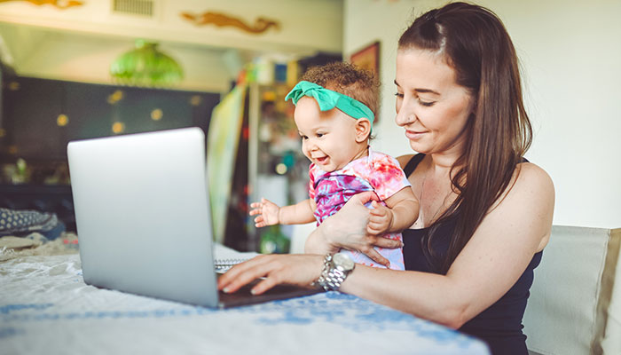New mother with baby joining parent support group online