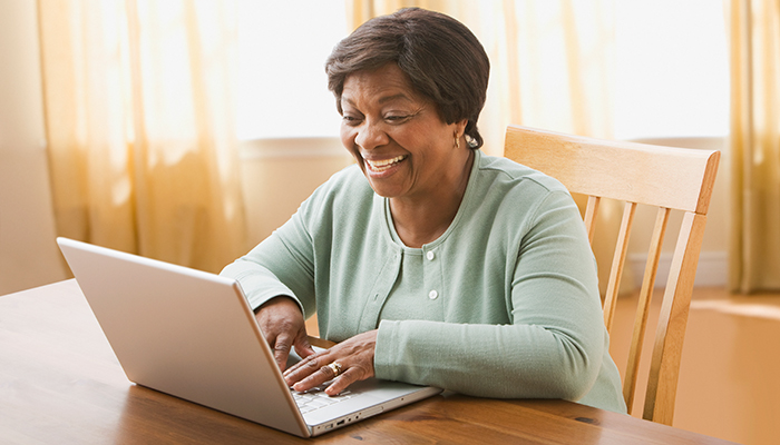 A senior woman is participating in an online support group