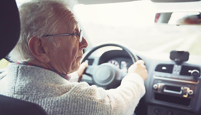 Senior adult male driving a car