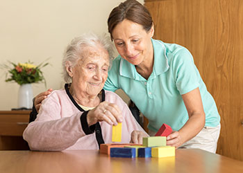 Senior woman plays with building blocks