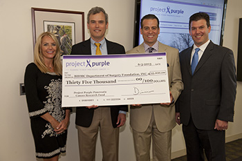 Project Purple presents BIDMC's Dr. James Moser with a check for pancreatic cancer research