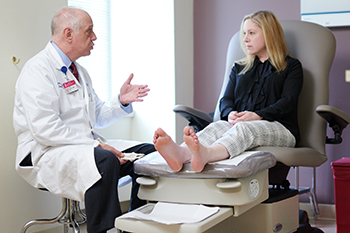 John Giurini, DPM of BIDMC talks to a patient about her foot problems.