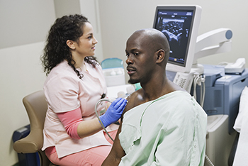 An x-ray technician performs and ultrasound exam on a patient's shoulder.