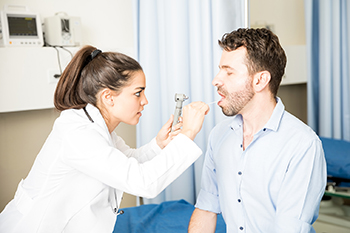 An otolaryngologist examines a patient's throat during an appointment.