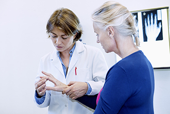 A rheumatologist is examining the joints of a patient's hand in an appointment.