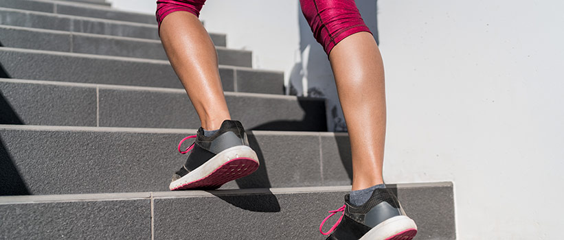 woman's legs seen running up outdoor stairs