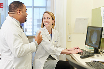 A BIDMC resident interacts with a Harvard faculty member.
